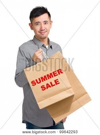Asian man hold with shopping bag and showing summer sale