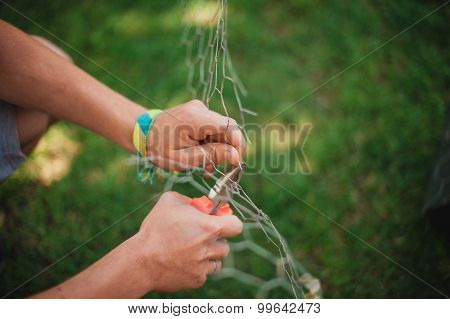 Men Hand, Cutting Wire Mesh Outside