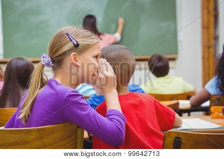 Student whispering into another students ear at the elementary school