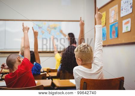 Students raising hands to answer a question at the elementary school