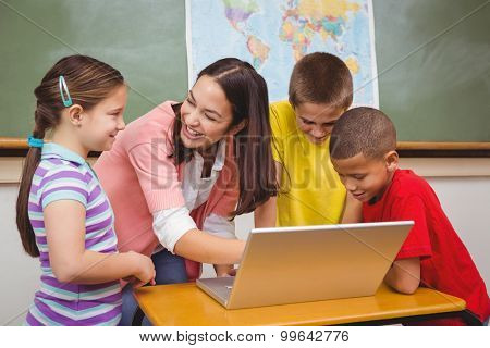 Students and teacher using a laptop at the elementary school