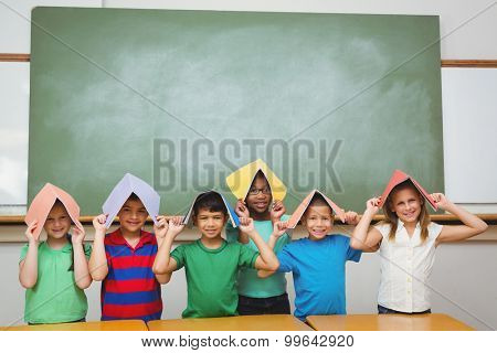 Students holding books over their heads at the elementary school