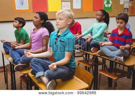 Pupils meditating on classroom desks at the elementary school