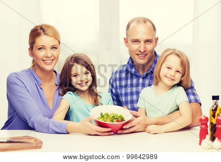 food, family, children, hapiness and people concept - happy family with two kids with salad at home
