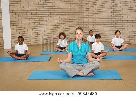 Students and teacher doing yoga pose at the elementary school