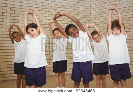 Happy students stretching out together at the elementary school