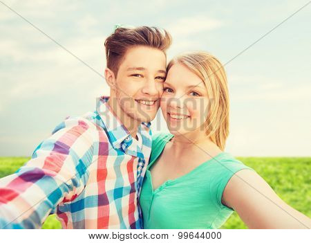 people, love, vacation, technology and summer concept - happy couple taking selfie with smartphone or camera over blue sky and grass background