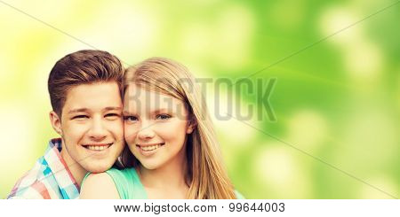 holidays, vacation, love, ecology and people concept - smiling teenage couple hugging over green background