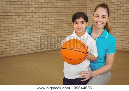Student holding basketball with teacher at the elementary school