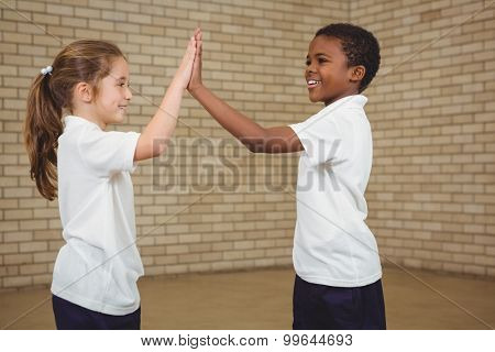 Happy pupils giving each other a high five at the elementary school
