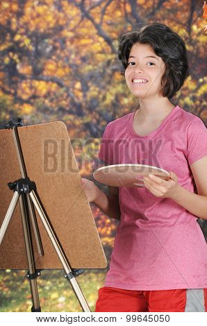 A pretty young teen looking up at the viewer as she paints on an easel outside in the fall.