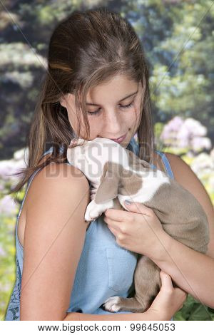 Close-up image of a pretty teen girl lovingly cuddling with her adorable sleeping puppy.