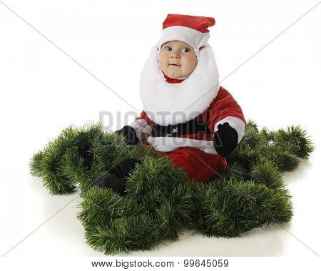 An adorable baby Santa sitting happily surrounded by green garland.  On a white background.