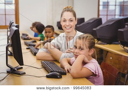 Teacher helping a student using a computer at the elementary school