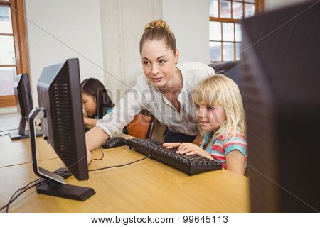 Teacher showing student how to use a computer at the elementary school