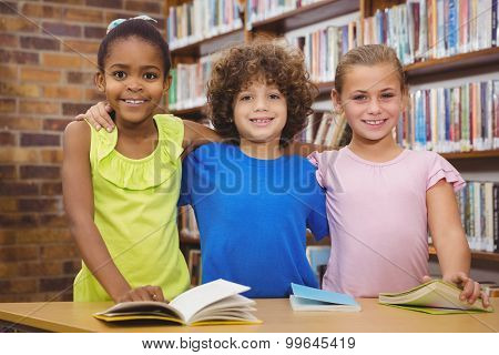 Happy pupils reading a library book at the elementary school