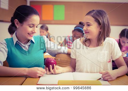 Pupil offering an apple to teacher at the elementary school
