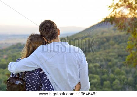 Loving Couple Hugging Outdoors With The Look At The Sunset. Romantic Sunset View.
