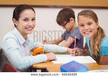 Teacher helping a little girl during class at the elementary school