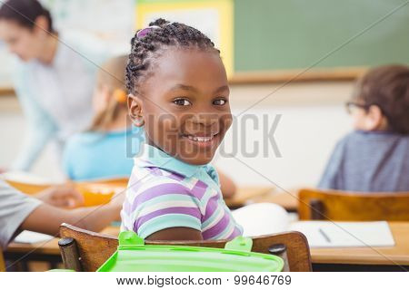 Pupil smiling at camera during class at the elementary school
