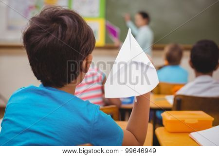 Pupil about to throw paper airplane at the elementary school