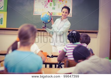 Pupils listening to their teacher holding globe at the elementary school