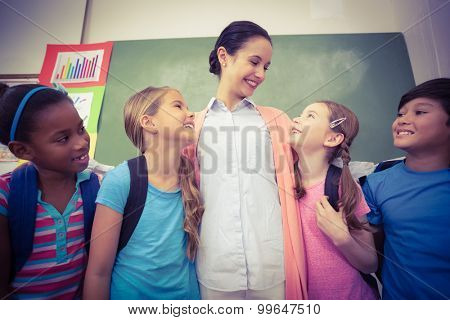 Teacher and pupils smiling in classroom at the elementary school