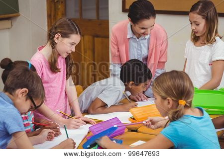 Teacher and pupils working at desk together at the elementary school