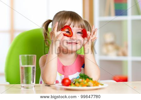 kid girl having fun with food vegetables in children room