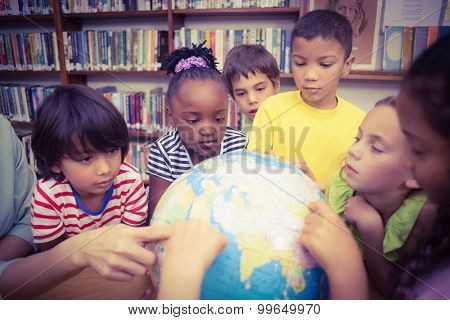 Pupils looking at globe in library at the elementary school