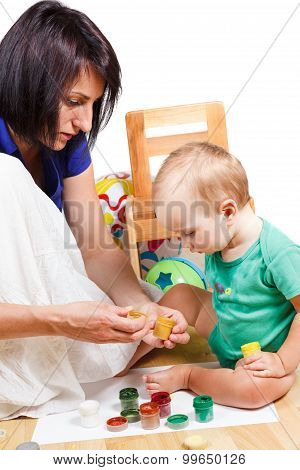 Mother Teaches The Kid To Paint Colors