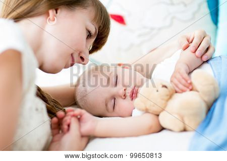 Happy mother cuddling her newborn baby