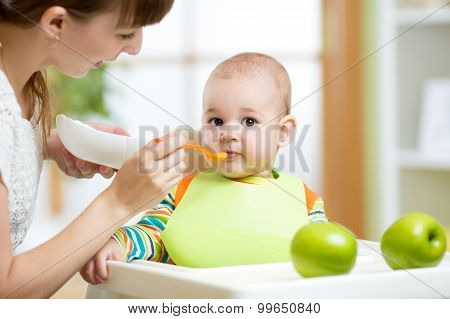 Happy mother spoon feeding her baby child