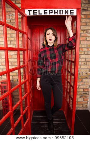 Beautiful Young Girl In Casual Style Standing In A Red Telephone Booth