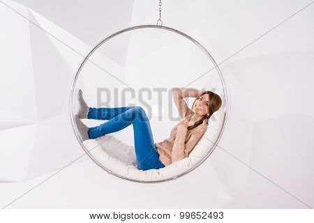 Girl Sits And Rests In A Transparent Glass Chair Against A White Wall With Geometric Shape And Laid