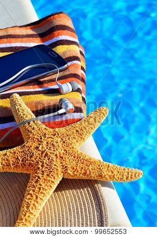 Beach Hat, Headphones, Bath Towel, Starfish Near The Swimming Pool