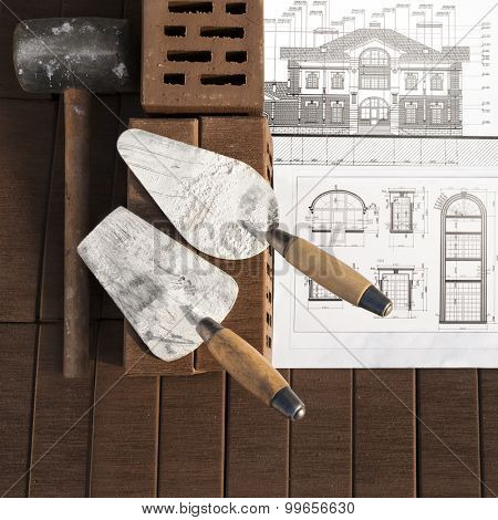Architectural project with brick and tools on brown brick background. Focus on foreground.
