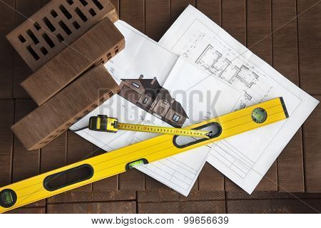 Architectural project with brick and tools on brown brick background