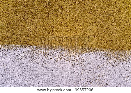 closeup of a rustic plastered wall painted in two colors, dark yellow and white, to use as a background