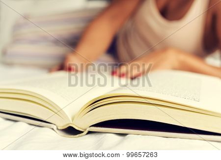a young caucasian woman in pajamas reading a book in bed