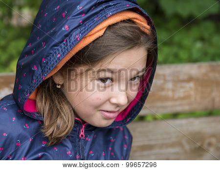 Outdoor portrait of a little girl in autumn jacket with a hood