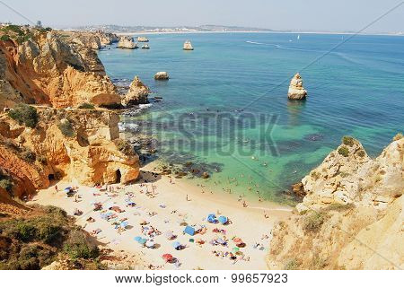 People relax at Praia da Dona Ana beach in Lagos, Portugal.