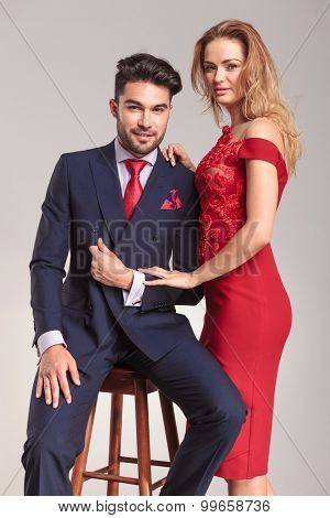 Smiling young elegant man sitting on a chair while his girlfriend is standing near him.