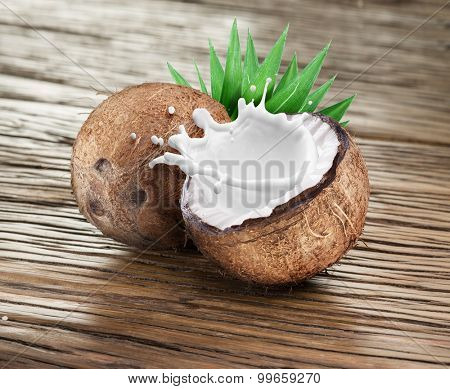 Coconut with milk splash inside on the wooden table.