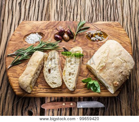 Ciabatta, olives and blue cheese on the wood.
