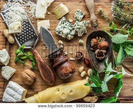 Different types of cheeses with nuts and herbs. Top view.
