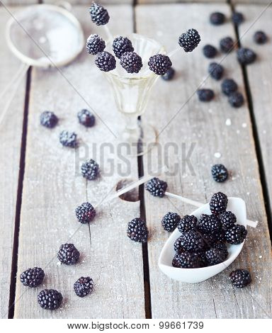 Blackberries in the little white bowl with basil leaf and sugar powder on the old wood background, s