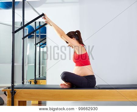 pregnant woman pilates reformer forward push through exercise workout at gym