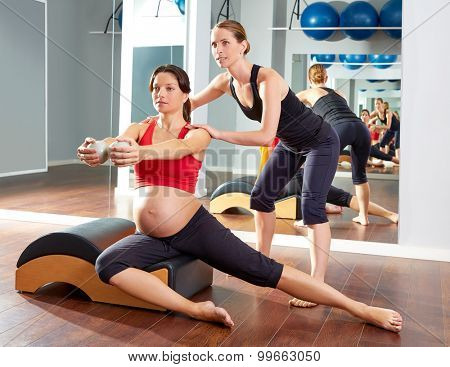 pregnant woman pilates side stretchs exercise workout at gym with personal trainer