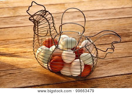 Eggs in a vintage hen shape basket on wood with blue easter white and brown colors